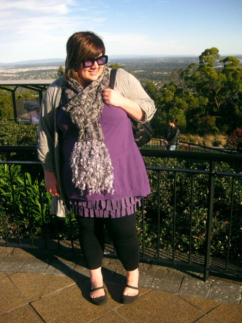 Photo of me on top of Mt Coot-tha. I'm wearing a long purple top over a fringey purple skirt, a grey long cardigan and scarf with black tights and shoes.