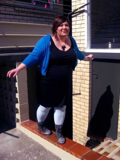 Photo of me balancing on a little ledge wearing a black dress, pale blue tights, grey boots and a blue sparkly cardigan.