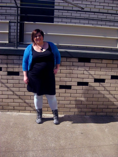 Photo of me posing for an outfit photo, wearing a black dress, pale blue tights, grey boots and a blue sparkly cardigan.