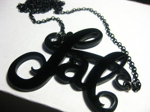 """A necklace that says """"fat"""" in curly lettering cut out of acrylic."""