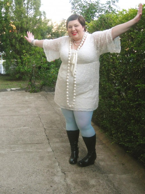 Outfit photo of me wearing a cream lace dress with big sleeves that are elbow length, mint coloured tights, black boots, and lots of cream and pearl necklaces. My arms are stretched out to show off the sleeves.