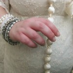A photo of my right hand (with lots of bracelets) lightly clasping a very long cream bead necklace.