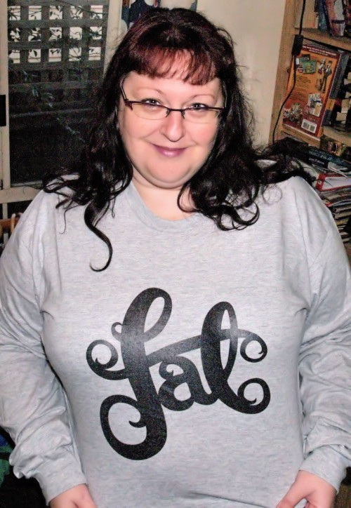 "A fat white woman with long dark hair wearing a grey long sleeved t-shirt with ""fat"" written in curvy typography."