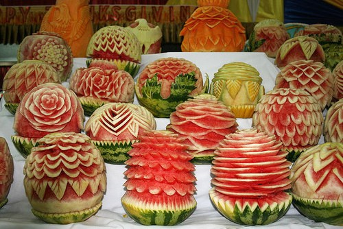 Photo of a bunch of gorgeous bright fucshia watermelons that have been carved in different, fancy ways.