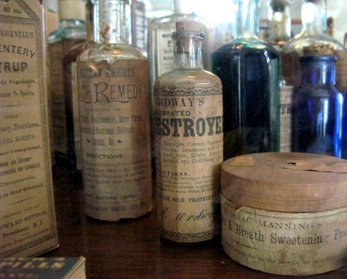 A photo of very old bottles and containers with aged labels that claim the contents to be remedies.