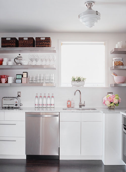 Photo of a crisp white kitchen with lots of light, floating shelves holding neatly arranged baskets, glasses and other things.
