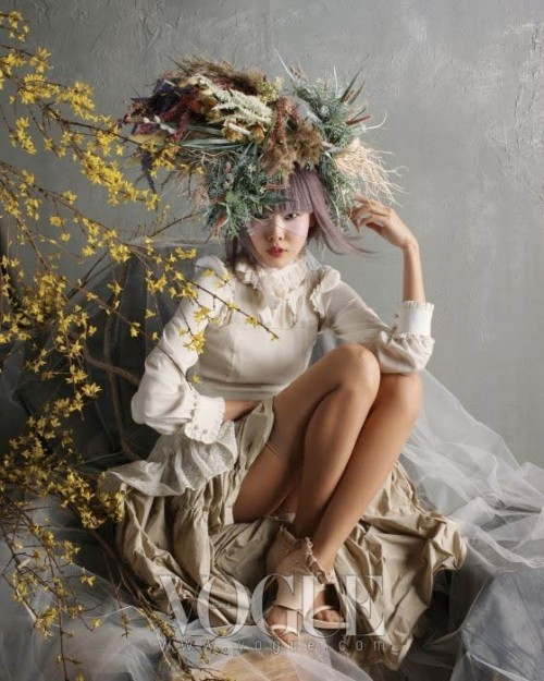Photo of a beautiful young Asian woman wearing a white dress with feathery plumes in her lilac coloured hair. She's sitting on a mountain of coffee coloured and white material, some tulle.