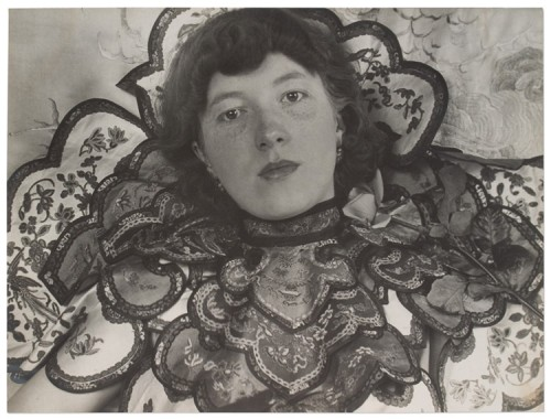 Black and white photo of a young pale skinned woman with chin length hair wearing an elaborately layered and embroidered neckpiece (or dress?) with scalloped edges. A rose sits on her left shoulder, she stares at the camera with an unsmilling, but not unkind, face