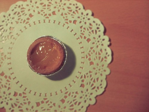 A photo of a very very small pie with a citrus butter type filling sitting on a paper doily shot from directly above.