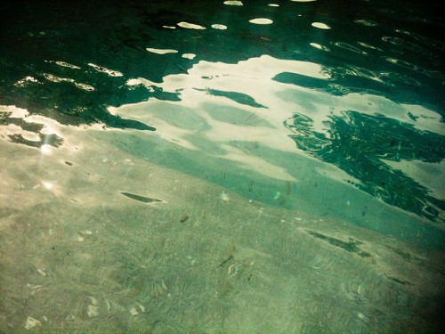 Photo of water in a pool, the light is dancing on the gently rippled surface and the water looks a deep greeny/ blue.