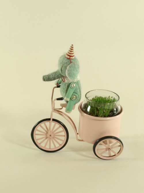 Photo of a miniature elephant in a party hat on a tricycle that holds a tiny glass jar full of grass.