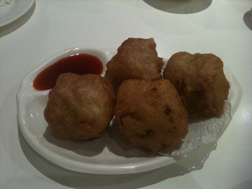 Photo of four huge fried dim sim with some sweet and sour sauce.
