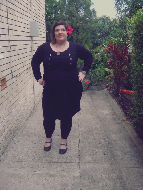 Outfit photo of me wearing a black dress with brass military style buttons at the bust, a long sleeve top under neath it and black leggings with black mary janes and a hibiscus flower behind my ear.