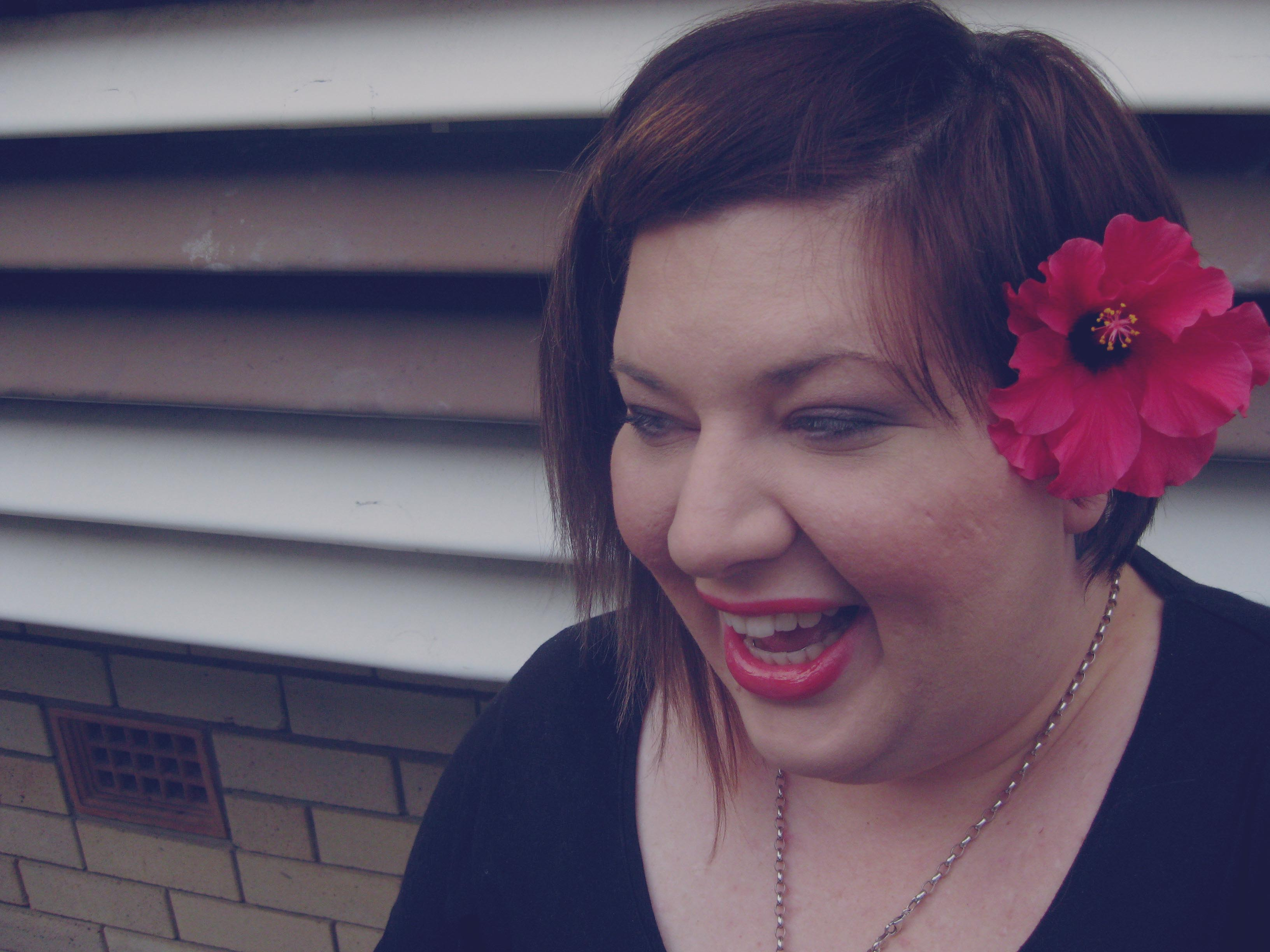 Photo of me laughing with a red hibiscus tucked behind my ear.