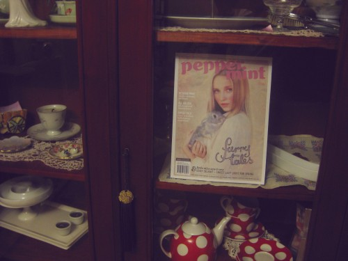 """Photo of a display cabinet with Peppermint magazine inside it along with other things like tea cups and saucers and candles. The magazine has a young blonde woman holding a rabbit on the cover, and my lettering in the lower right says """"furry tales""""."""