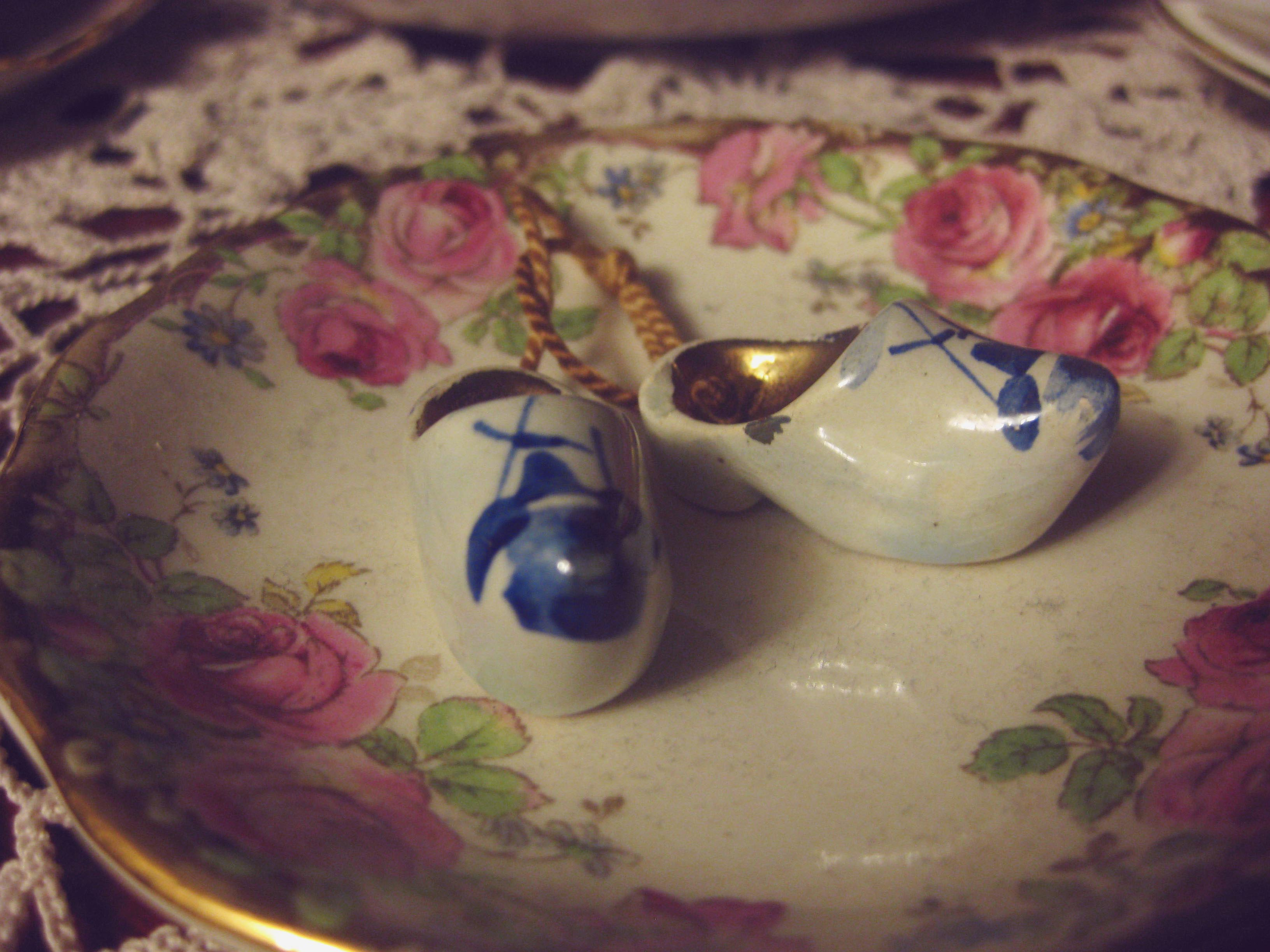 Macro shot of a pair of tiny white porcelain clogs with a blue windmill on each toe. They sit in a small condiment bowl that is bordered with a beautiful floral pattern with large pink roses.