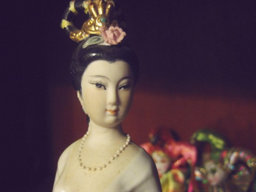 Macro photo of the face of a Chinese woman statuette, her hair is up and a  fancy ornament adorns her head. She wears a string of pearls and a white gown with a low neckline.