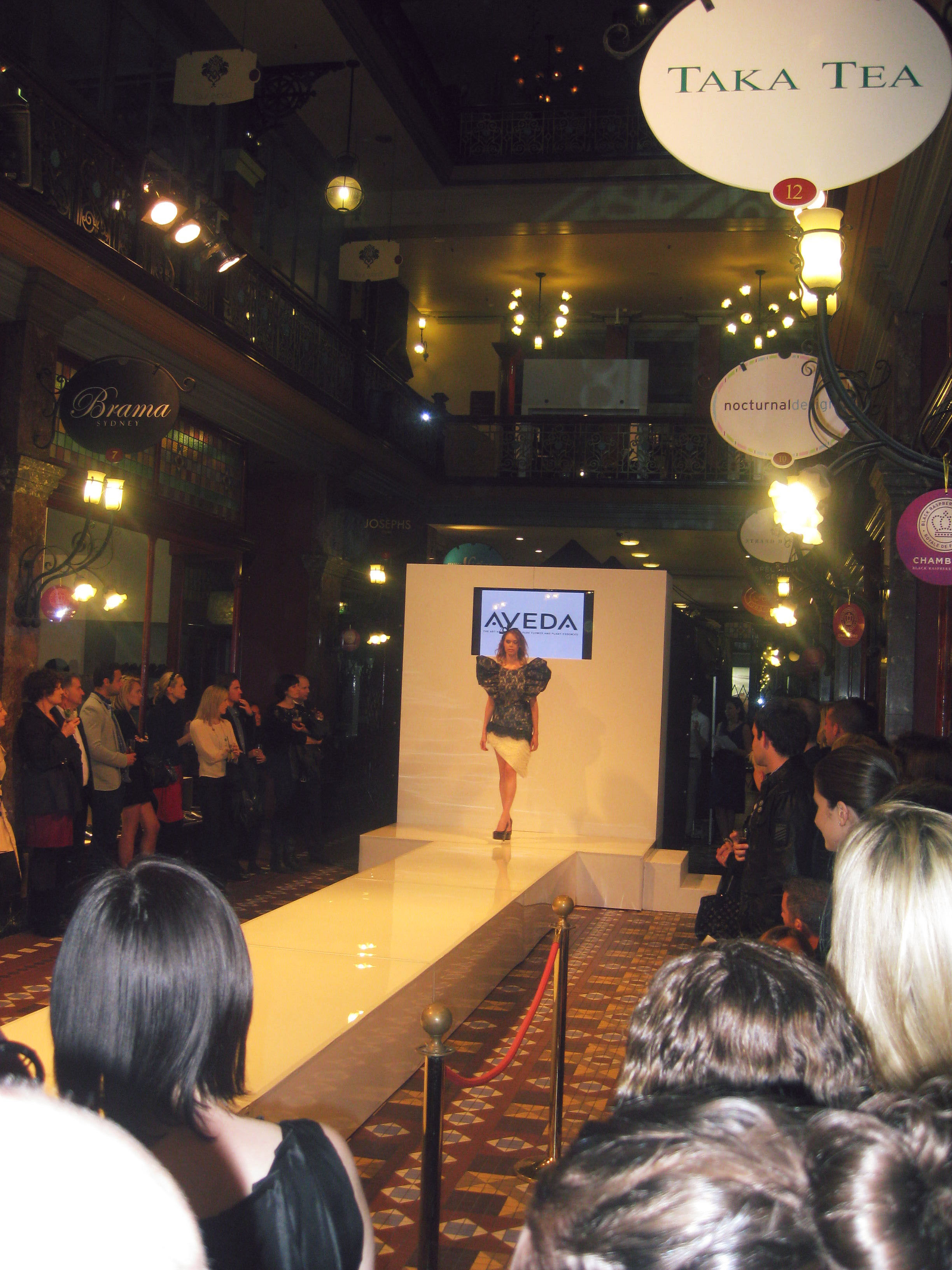 A model walks down the catwalk wearing a black and white patterned dress with huge ruffled shoulders.
