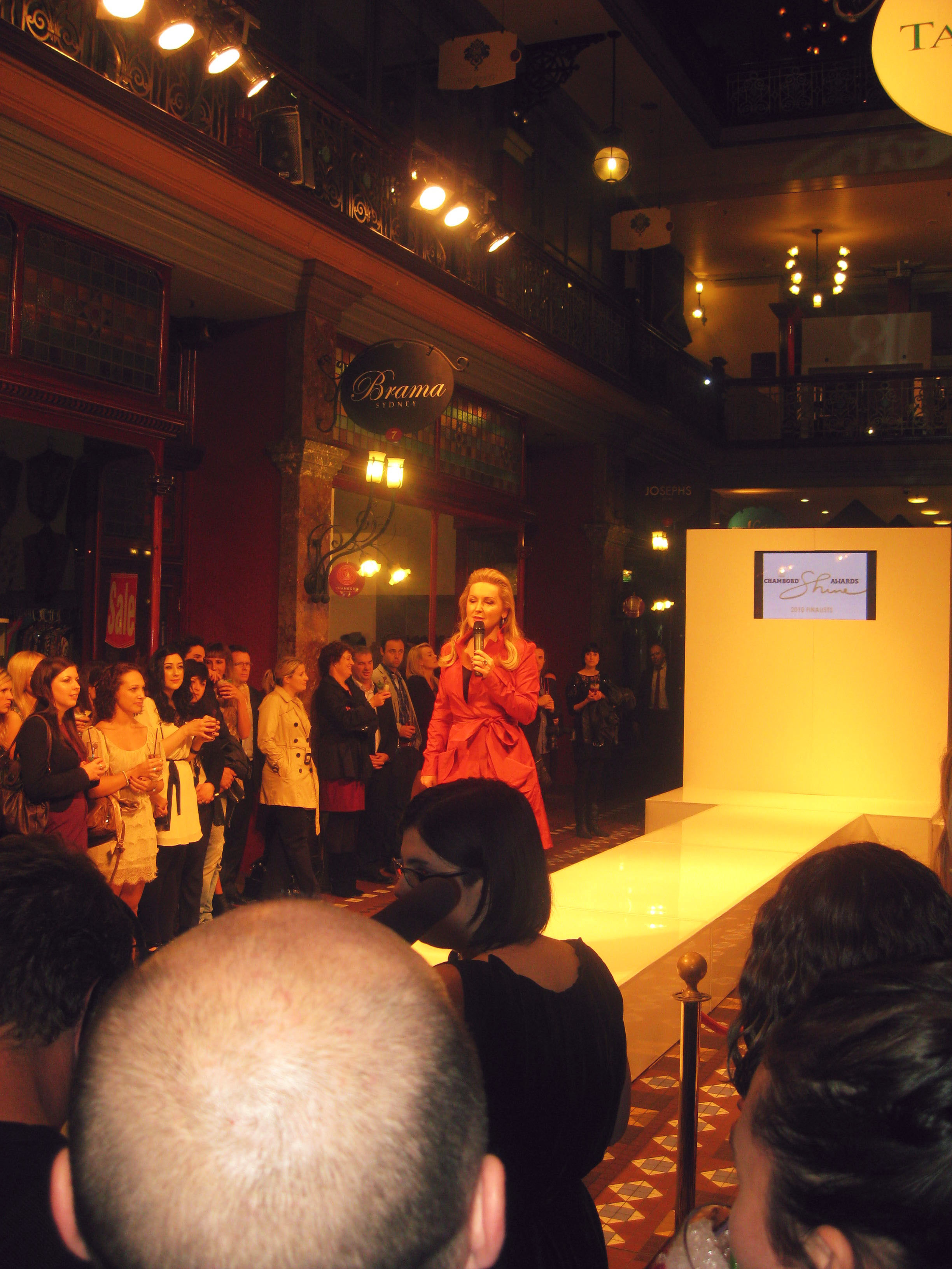 A woman with long blonde hair in a red jacket stands at the end of a white runway with a microphone, people crowded around.