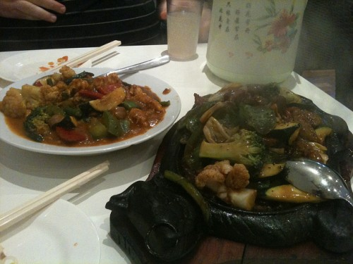 "Photo of two large dishes: at rear satay ""chicken"" and in front some sizzling beef in pepper sauce."