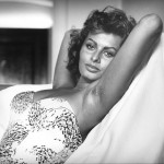 A black and white photograph of Sophia Loren reclining in a strapless top, her arms behind her head. Her armpits are scattered with fine hair.