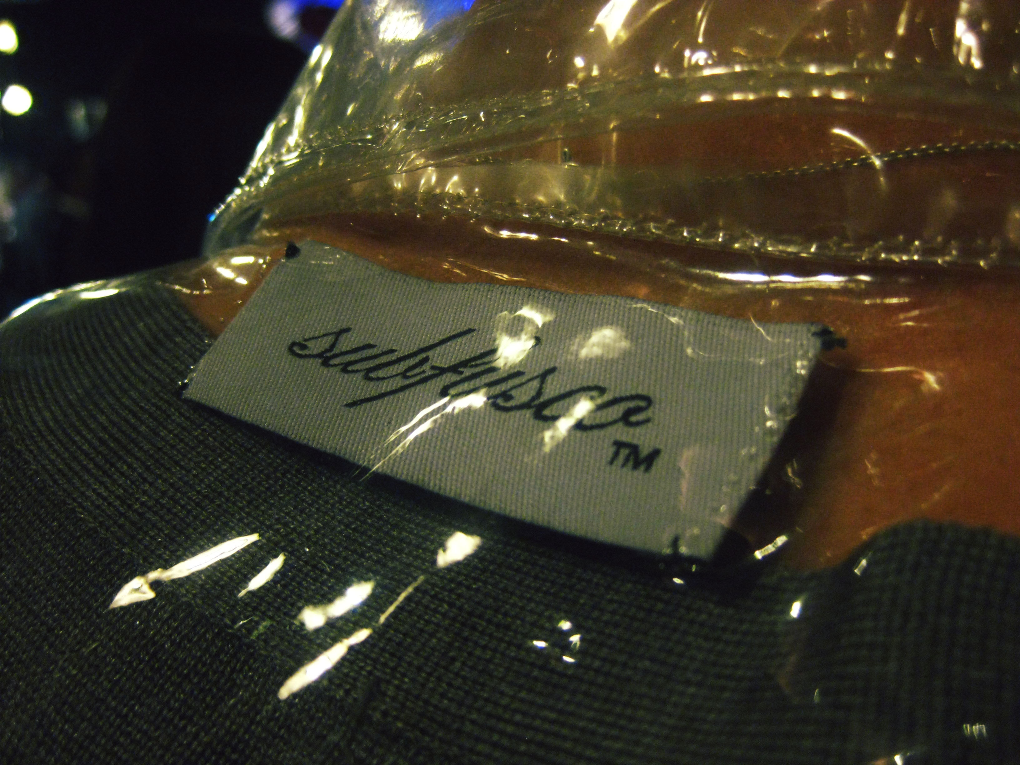 Close up of the Subfusco label sewn into a see-through plastic jacket.