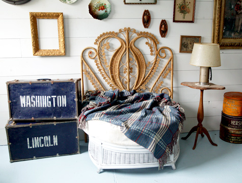 Photo of a chair with a big ornate backing made of cane, there's also a bunch of old pictures and frames on the wall.