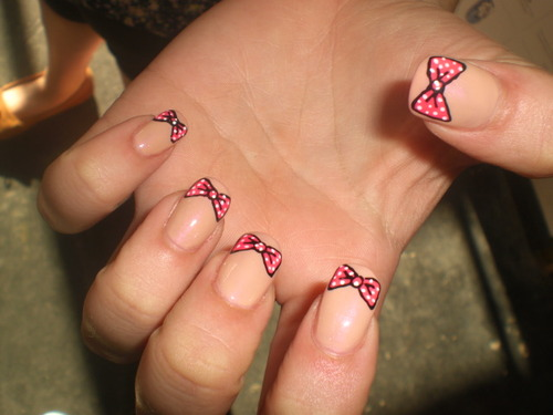 Photograph of a pale skinned hand displaying a manicure where the nail is painted beige (to match the skin tone) and a pink polka-dotted bow sits on the top of each nail.