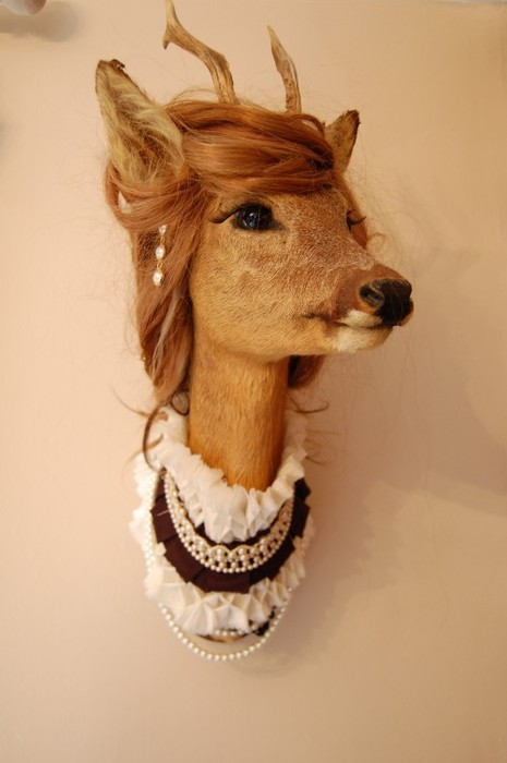 A photo of a wall mounted deer head that has been dressed up in a honey coloured wig, earrings and a frilly neckpiece trimmed with pearls.