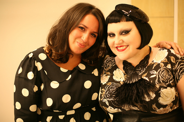 Photo of Sakina wearing the polka dot dress with Beth Ditto, who wears the floral dres with a feathered statement necklace and a small sequinned beret like headpiece.