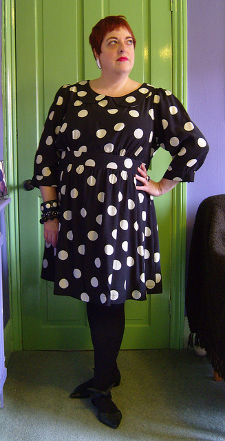 Photo of an older pale skinned woman with short dark hair wearing the polka dot dress.