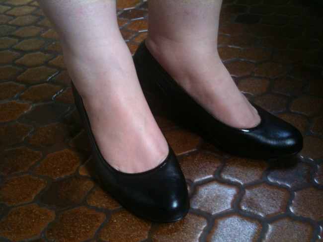 Close up shot of my feet wearing black court style shoes with a low wedge heel. They're a bit shiny!
