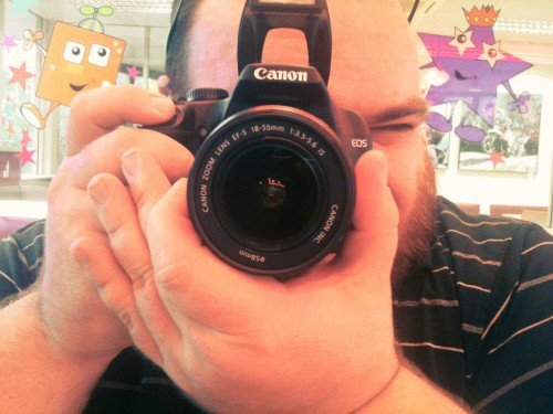 Photo of Nick looking through the viewfinder of a Canon EOS 1000D.
