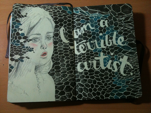 "Photo of a drawing across two pages of a moleskine, a pencil sketch of a young girl with rosy cheeks and lips sits agains a black and dark teal fishnet pattern with ""I am a terrible artist"" written in it."