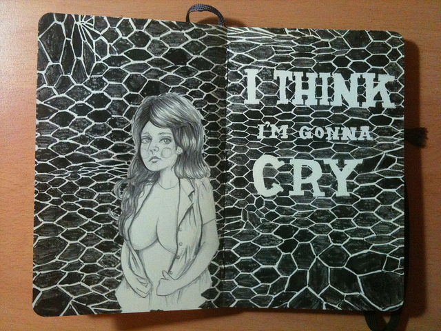 "Photo of a drawing across two moleskine pages: a pencil drawing of a young woman with long hair, and an open shirt that just covers her breasts against an undulating fishnet pattern which has the words ""I think I'm gonna cry"" written in it."