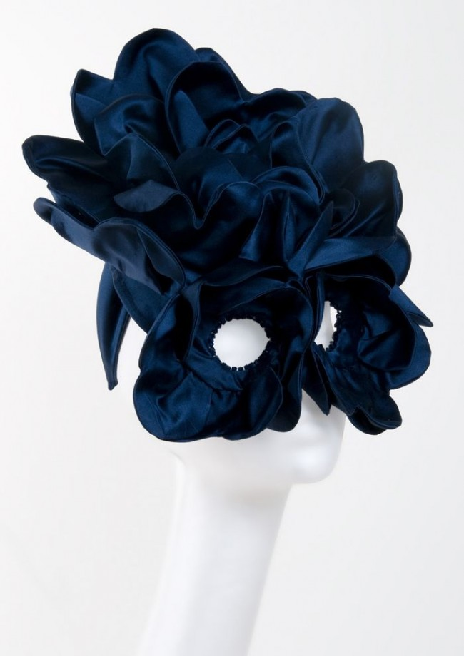 Photo of a huge black silk headpiece on a white model head, it's all ruffly and circles the eyes like a mask.