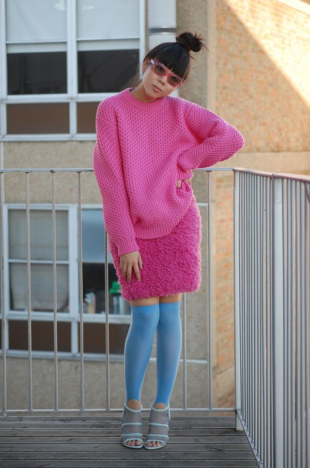 Outfit photo of a young, thin woman with milky tea coloured skin and black hair with a blunt fringe wearing an oversized pink knit sweater with a pink skirt that looks like cut pile carpet. She also wears blue shoes with blue stockings that come up over her knees.