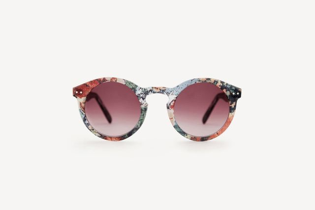A pair of round sunglasses with floral frames and burgundy graduated frames.