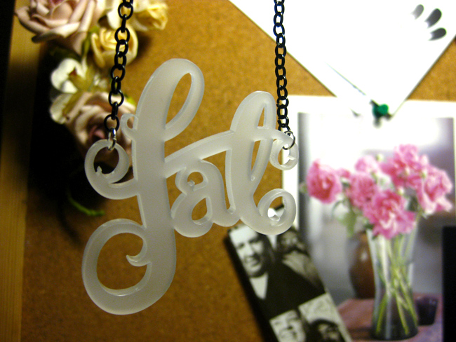 Close up shot of my fat necklace cut in a frosted white acrylic. It's hanging in front of my pin board which has some fake flowers, photobooth photos and a photo of a nice floral arrangement pinned to it.