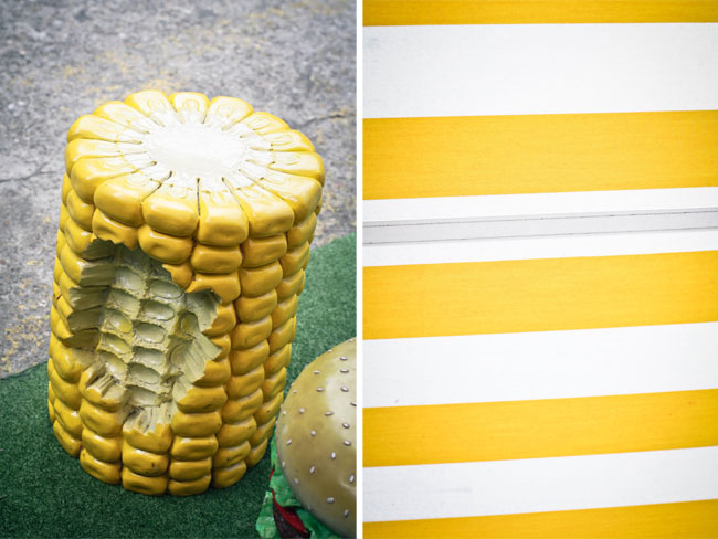 "Collage of two photos: left is a giant cord on the cob used as a stool to sit on, there's a chunk of it been ""bitten"" off!; right is a detail shot of the canvas awning which is yellow and white striped."