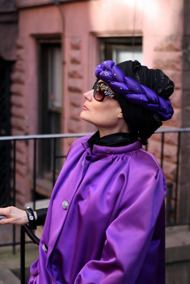 Photo of an older woman with pale skin wearing a black hair wrap with a purple plaited headband around it, as well as a magnificent purple coloured jacket. She wears dark sunglasses and is gazing off into the distance in profile.