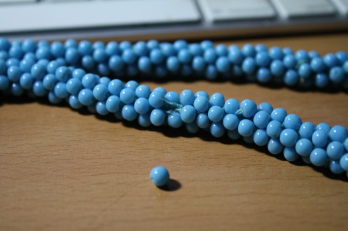 A macro photo of a multistrand turquoise beaded necklace with a broken thread poking out of the tightly beaded rope. The offending single bead sits in front of the necklace.