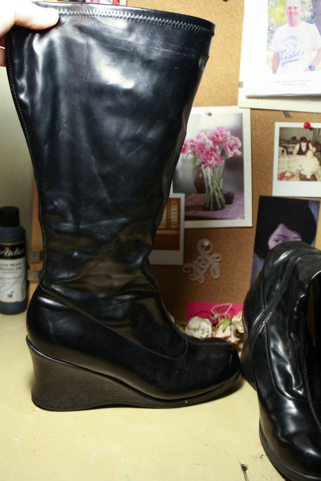 A pair of black PVC boots with a wedge.