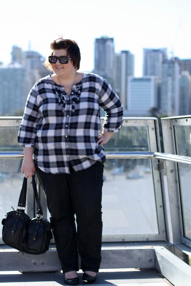 Outfit photo of me wearing a black checked tunic top with small ruffles down the button front, black jeans and round toe black wedges with a black bag. Behind me is a blurry backdrop of the CBD of Brisbane.