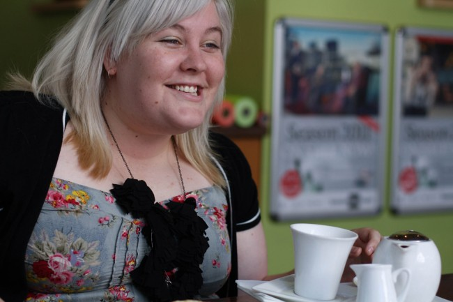 Photo of a pale skinned young woman with almost white shoulder length hair talking and smiling. There's a tea set at her hand.