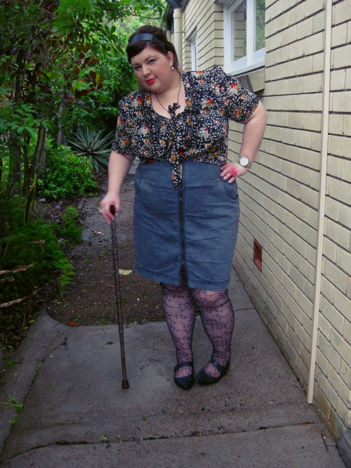Outfit photo of me wearing a dark patterned blouse and a grey high waised pencil skirt with a zip up the front. I'm wearing lace fishnet stockings and flat pointy mary jane shoes. I'm leaning on a leopard printed walking stick.