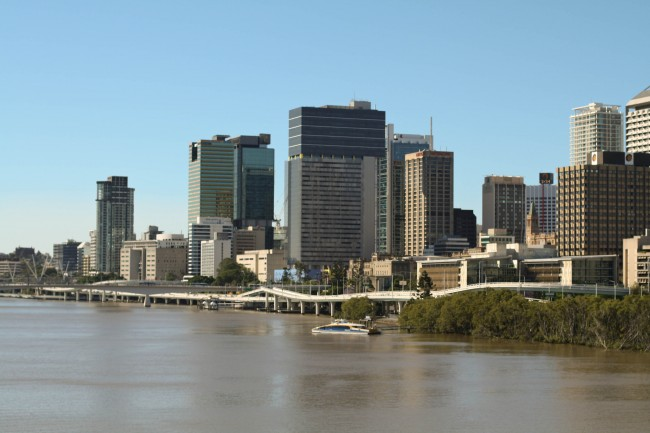 Photo of the Brisbane CBD as seen from the middle of the Goodwill Bridge. The sky is blue but the river looks brown after the recent rain.