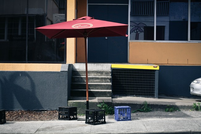 Photo of a cafe style umbrella on a footpath with  three milkcrate seats underneath it.