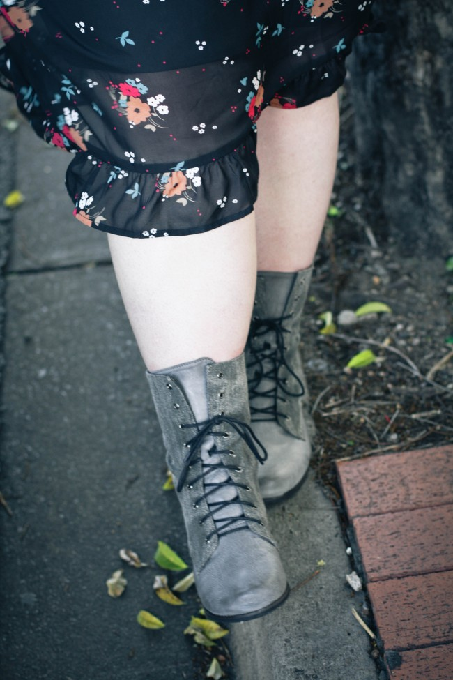 Photo of my legs and feet in grey boots walking along a gutter, you can see a bit of the sheer fabric of my skirt in the frame.