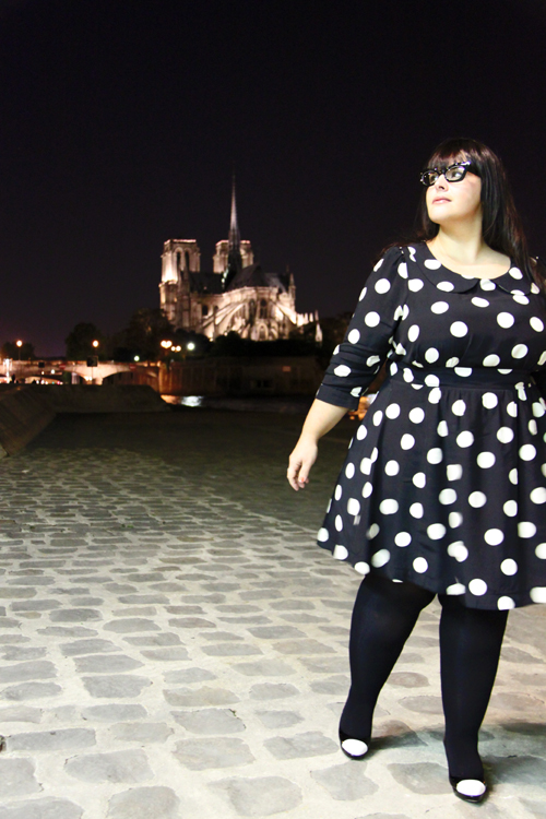 Photo of a fat young pale skinned woman with long dark hair and dark rimmed glasses wears the polka dot dress in front of what looks like a fancy building!